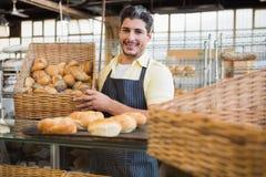 拿着面包的篮子愉快的工作者画象 库存图片