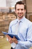 使用数字式片剂的经理在仓库 免版税库存图片