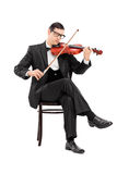 弹小提琴的古典音乐家供以座位在椅子 免版税库存照片