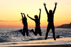 朋友现出轮廓跳愉快在海滩在日落 免版税库存照片
