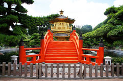 有红色桥梁的金黄亭子在中国庭院里 免版税库存图片