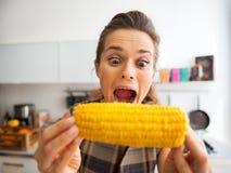 Αστεία νέα γυναίκα που τρώει το βρασμένο καλαμπόκι Στοκ Εικόνες