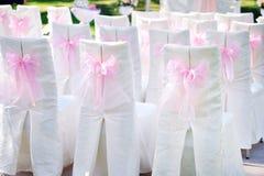 用在椅子婚礼的桃红色弓装饰 免版税库存图片