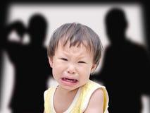 有她战斗的父母的哭泣的女孩 免版税库存照片