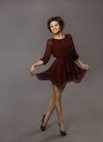 妇女愉快的跳舞,摆在红色礼服的微笑的高兴的女孩 图库摄影