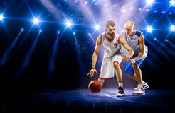 聚光灯的两个蓝球运动员 免版税库存图片