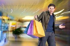 有购物袋的微笑的英俊的人 免版税图库摄影