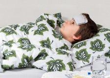 病的小男孩在床上 免版税图库摄影