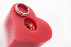 定婚戒指和蜡烛在心脏塑造 库存图片