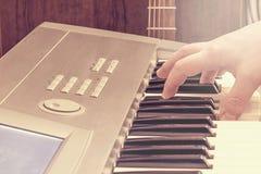 在键盘和吉他的男性手 图库摄影