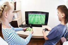Παιδιά που παίζουν στην κονσόλα παιχνιδιών για να παίξει το ποδόσφαιρο Στοκ Εικόνες