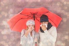 Σύνθετη εικόνα του ζεύγους στη χειμερινή μόδα που φτερνίζεται κάτω από την ομπρέλα Στοκ Εικόνες
