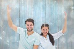 坐与胳膊的逗人喜爱的夫妇的综合图象被举 免版税库存照片