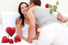 Σύνθετη εικόνα του συζύγου που δίνει ένα τριαντάφυλλο και ένα φιλί στην όμορφη σύζυγό του Στοκ Εικόνες