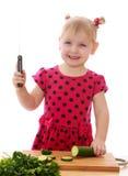 有刀子的微笑的小女孩切了黄瓜 免版税库存照片