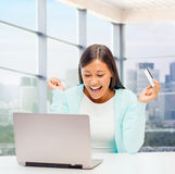 有膝上型计算机和信用卡的愉快的女实业家 免版税库存图片