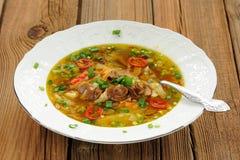 狂放的蘑菇和蔬菜汤用在白色板材的辣椒 库存照片