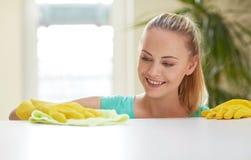愉快的妇女清洁桌在家厨房 免版税库存照片