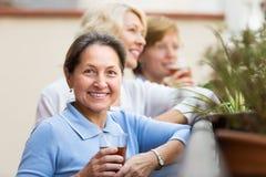 喝茶的三名妇女在阳台 免版税库存照片