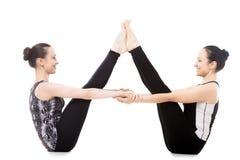 平衡的棍子瑜伽姿势的两个信奉瑜伽者女性伙伴 图库摄影