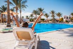 一张轻便折叠躺椅的愉快的女孩在夏天,在度假 免版税库存照片