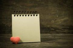 Λαβή εγγράφου σημειώσεων κοντά στην καρδιά Στοκ φωτογραφία με δικαίωμα ελεύθερης χρήσης