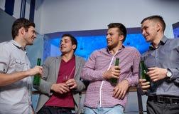 小组男性朋友用啤酒在夜总会 图库摄影