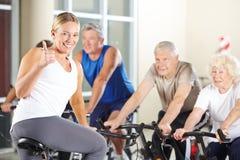 Инструктор фитнеса в спортзале держа большие пальцы руки вверх Стоковые Изображения RF