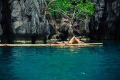 放松在木筏的美丽的妇女在热带盐水湖 免版税库存照片