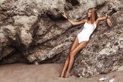 有棕褐色的美丽的女孩在泳装坐岩石在海滩 库存图片