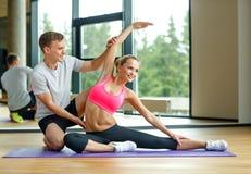 Χαμογελώντας γυναίκα με την αρσενική άσκηση εκπαιδευτών στη γυμναστική Στοκ Εικόνα