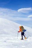 远足在雪靴的山的冬天有背包和帐篷的 免版税图库摄影