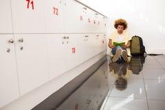 坐在办公室走廊的偶然年轻人 免版税库存图片