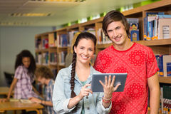 使用数字式片剂的学生在图书馆 库存照片