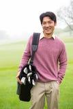 站立的高尔夫球运动员拿着他的微笑对照相机的高尔夫球袋 库存照片