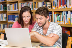 使用膝上型计算机的大学生在图书馆 免版税库存照片