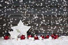 在堆的星状圣诞节装饰圣诞节电灯泡桂香星反对木墙壁雪的雪落 免版税库存照片