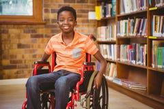 坐在轮椅的男孩画象在图书馆 免版税库存图片