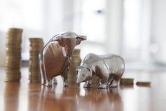 股市、牛市与熊市,小雕象,堆硬币 免版税库存照片