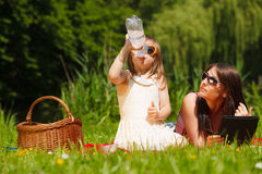 母亲和女儿有野餐在公园 免版税图库摄影