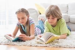 兄弟姐妹阅读书,当说谎在地毯时 库存图片