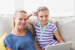 有在家使用在沙发的母亲的愉快的女孩膝上型计算机 免版税库存照片