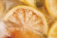 在冰块,结冰,特写镜头的橙色切片 免版税库存照片
