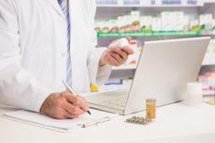 Φαρμακοποιός που γράφει στην περιοχή αποκομμάτων και που κρατά το φάρμακο Στοκ εικόνες με δικαίωμα ελεύθερης χρήσης