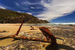在岩石的生锈的船锚在海岸 库存图片