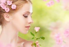 Πρόσωπο ομορφιάς της νέας όμορφης γυναίκας με τα ρόδινα λουλούδια στο εκτάριό της Στοκ Εικόνες