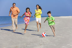 踢在海滩的家庭橄榄球足球 库存照片