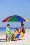 母亲父亲女儿儿子做父母在海滩的儿童家庭 库存照片