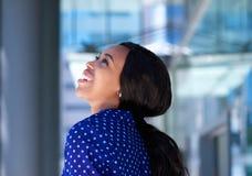 Εύθυμη νέα μαύρη επιχειρησιακή γυναίκα που γελά υπαίθρια Στοκ Φωτογραφία