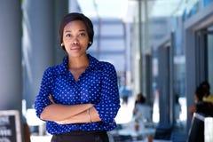 站立在城市的确信的年轻非裔美国人的妇女 免版税库存照片